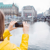 Student is photographing the Hamburg city hall with her smartphone.